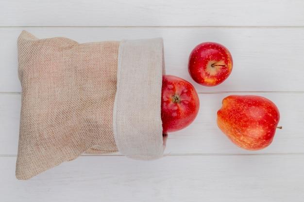 Widok z góry czerwonych jabłek wysypujących się z worka na drewnianym stole