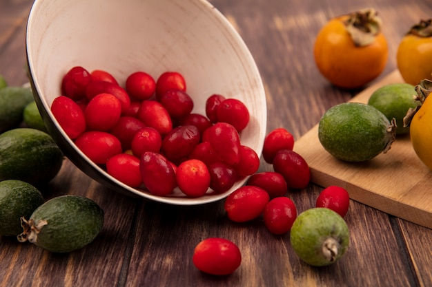 Widok z góry czerwonych kwaśnych wiśni derenia wypadających z miski z persimmon i feijoas odizolowanymi na drewnianej ścianie