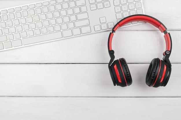 Widok z góry czerwonych słuchawek i białej klawiatury