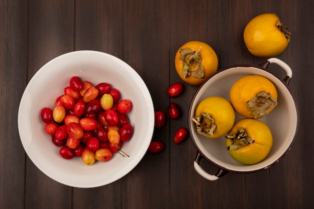 Widok z góry czerwonych wiśni dereń na białej misce z owocami persimmon na misce na drewnianej ścianie