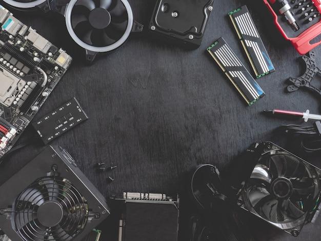 Widok z góry części komputera z dyskiem twardym, pamięci ram, procesorem, kartą graficzną i płytą główną na czarnym tle tabeli.