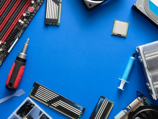 Widok z góry części komputera z dyskiem twardym, ram, procesorem, kartą graficzną i płytą główną na niebieskim tle tabeli.