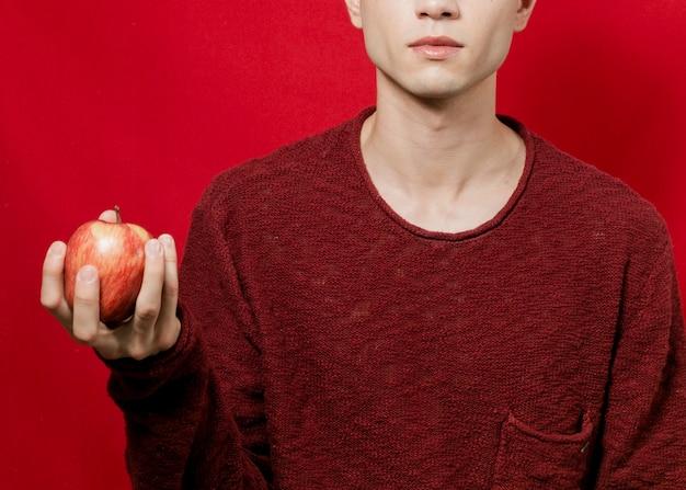 Widok z góry człowieka trzymającego jabłko w prawej ręce