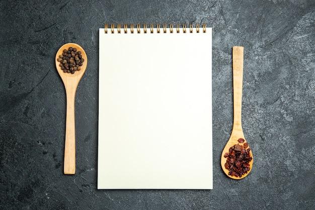 Widok z góry czysty notatnik z łyżkami na szarej przestrzeni
