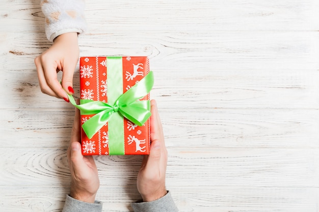 Widok z góry dając i otrzymując prezent na drewnianym. obecny w męskich i żeńskich rękach. miłość . copyspace