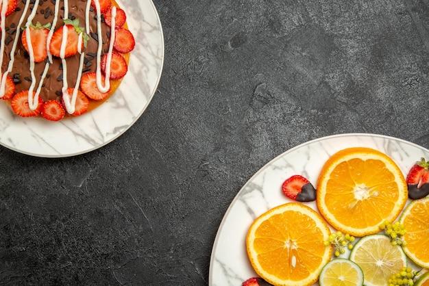 Widok z góry dania z bliska na talerzu z owocami cytrusowymi i truskawkami w czekoladzie oraz ciasto z czekoladą i truskawkami