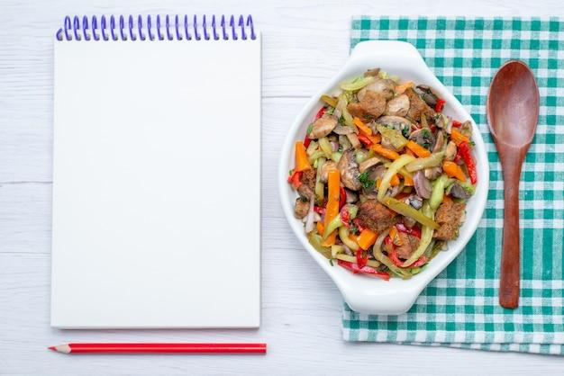Widok z góry danie mięsne w plasterkach z gotowanymi warzywami wewnątrz płyty wraz z notatnikiem na jasnym tle jedzenie posiłek mięso warzywne
