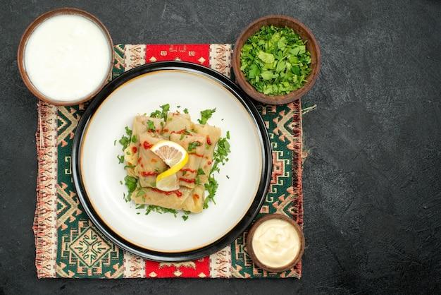 Widok z góry danie na obrusie apetyczna gołąbka na obrusie w wielobarwną kratkę i miski ziół biały sos i kwaśna śmietana po lewej stronie ciemnego stołu