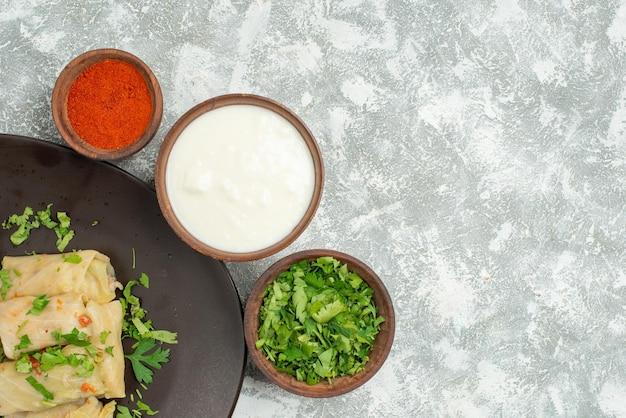 Widok z góry danie na stole gołąbka kapusta w talerzu obok miski z ziołami pachnącymi przyprawami i kwaśną śmietaną po lewej stronie szarego stołu