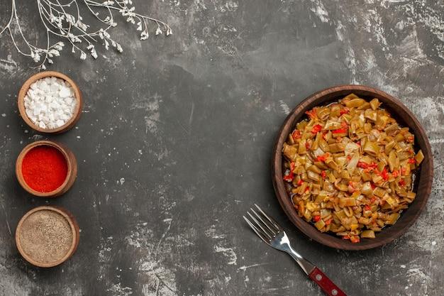 Widok z góry danie z zielonej fasoli trzy miski przypraw obok talerza zielonej fasoli z pomidorami i widelcem na czarnym stole