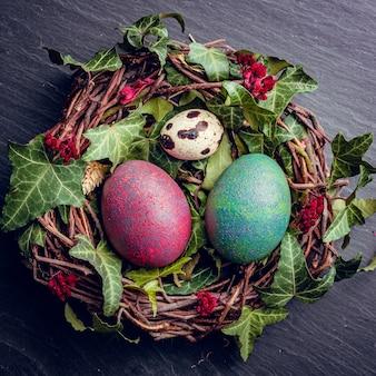 Widok z góry dekoracyjnego ptasiego gniazda z malowanymi jajkami wielkanocnymi