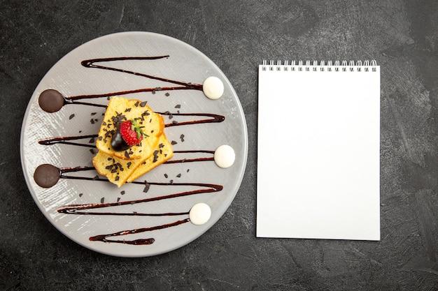 Widok z góry deser biały notatnik obok szarego talerza apetycznego ciasta z truskawkami i sosem czekoladowym po lewej stronie ciemnego stołu