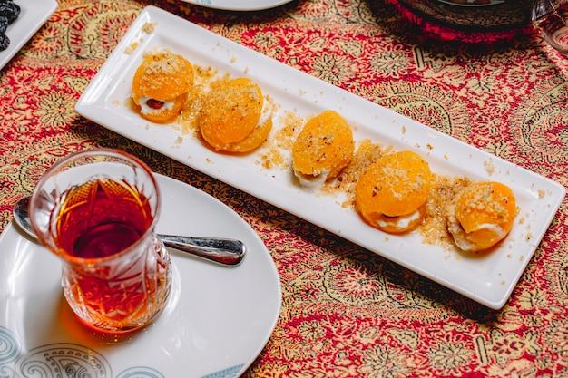 Widok z góry deser słodkie brzoskwinie z orzechami i śmietaną i szklanką herbaty