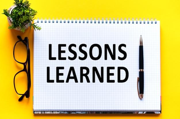 Widok z góry, dłoń trzymająca ołówek, pisząca lista nauczonych lekcji z notatnikiem, długopisem, okularami, kalkulatorem i zielonym kwiatkiem na żółtym stole. koncepcja biznesu i edukacji