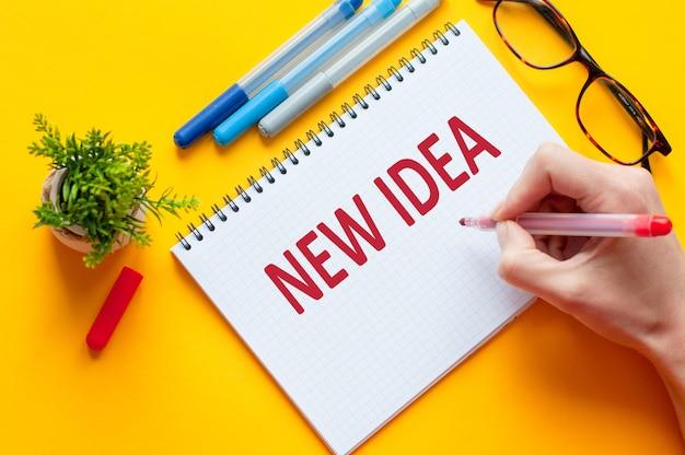 Widok z góry, dłoń trzymająca ołówek, pisząca lista nowych pomysłów z notatnikiem, długopisem, okularami, kalkulatorem i zielonym kwiatkiem na żółtym stole. koncepcja biznesu i edukacji
