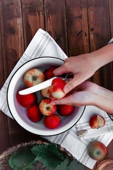 Widok z góry dłoni cięcia jabłka nad miską z czerwonymi jabłkami