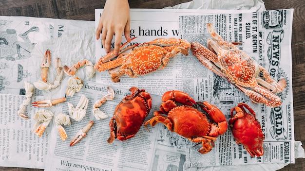 Widok z góry dłoni dotykającej gotowanych na parze krabów kwiatowych i olbrzymich krabów błotnych z oddzielonymi częściami krabów gotowanych na parze