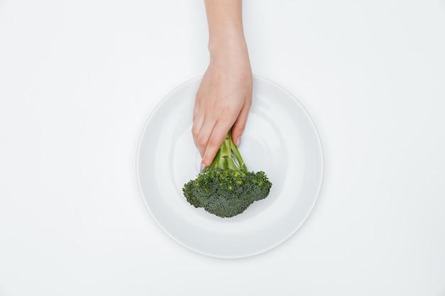 Widok z góry dłoni kobiety kładącej brokuły na talerzu