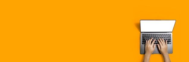 Widok z góry dłoni osoby piszącej wiadomość na laptopie przy biurku, kopiowanie miejsca na banery reklamowe, izolowane na pomarańczowym tle i ścieżce przycinającej.