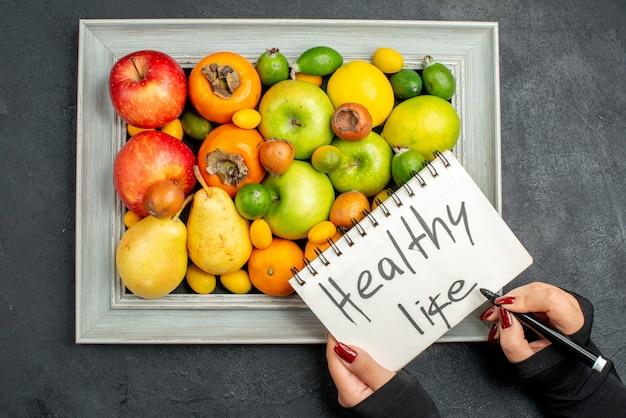Widok z góry dłoni piszącej zdrowe życie na spiralnym notatniku na zbiór świeżych owoców w ramce na zdjęcia na ciemnym tle
