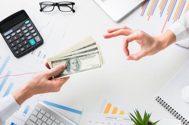 Widok z góry dłoni przyjmującej pieniądze na biurku