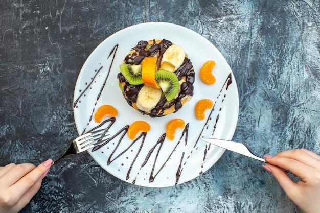 Widok z góry dłoni trzymającej nóż widelca na naleśnikach w stylu amerykańskim wykonanych z jogurtu naturalnego i ułożonych warstwami owoców ozdobionymi czekoladą na białym talerzu na lodowym tle