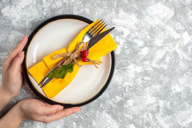 Widok z góry dłoni trzymającej zestaw sztućców do posiłku na białym talerzu po prawej stronie na powierzchni lodu
