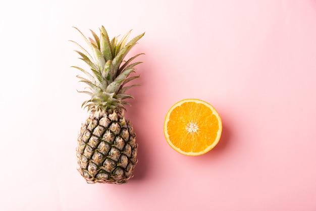 Widok z góry dojrzałego ananasa i pomarańczy na różowym pastelu