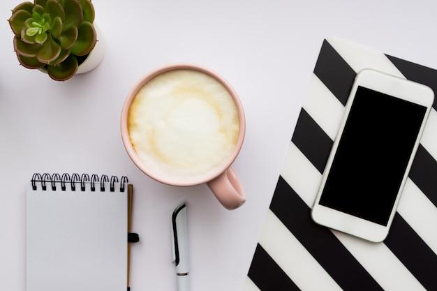 Widok z góry domowego biura. smartphone, pusty notatnik i filiżanka cappuccino na białej ścianie