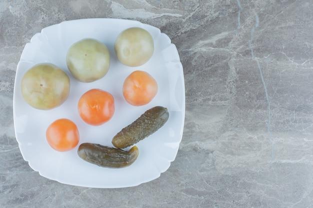 Widok z góry domowej roboty marynaty. niedojrzałe pomidory i ogórek na białym talerzu.