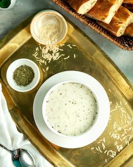 Widok z góry dovga-jogurtowa tradycyjna azerska zupa z ryżem i suszonymi ziołami na tacy