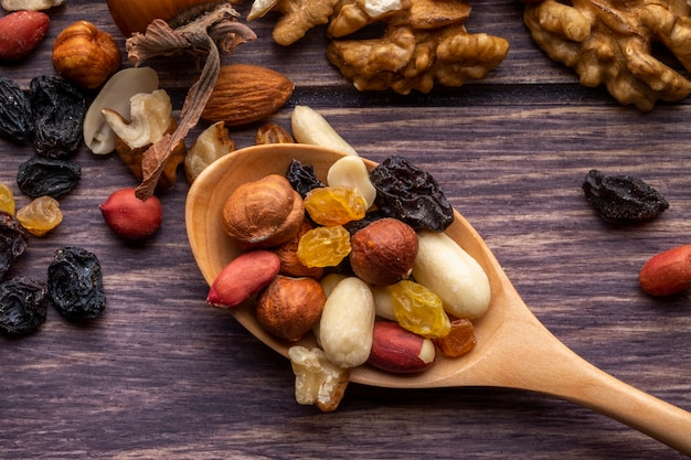 Widok z góry drewnianą łyżką z orzechami i rodzynkami, orzeszki ziemne i migdały na drewnianym stole