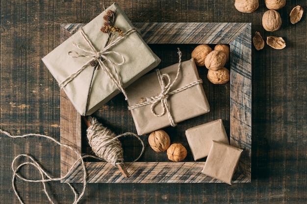 Widok z góry drewniana rama z prezentami i orzechami