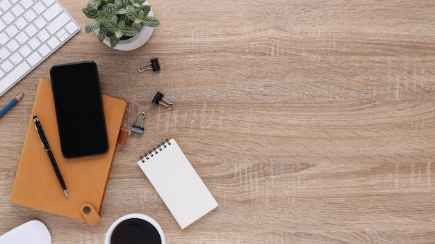 Widok z góry drewniane biurko biurowe z komputerem i materiałami biurowymi. płaski stół roboczy z pustym notatnikiem, klawiaturą, długopisem, smartfonem i filiżanką kawy. skopiuj miejsce na treści reklamowe.
