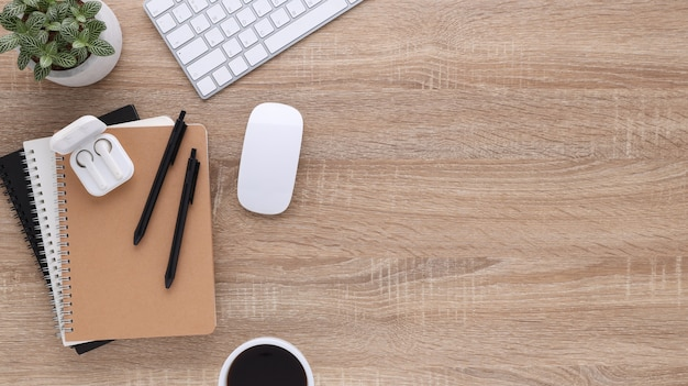 Widok z góry drewniane biurko biurowe z komputerem i materiałami biurowymi. płaski stół roboczy z pustym notatnikiem, klawiaturą, słuchawkami, kwiatami i filiżanką kawy. skopiuj miejsce na treści reklamowe.