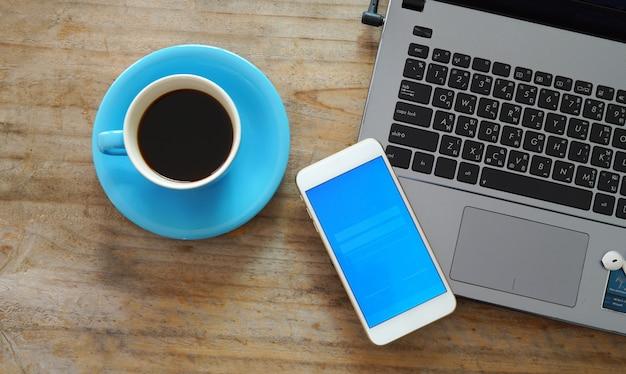Widok z góry drewniany pulpit z klawiaturą laptopa, filiżanka kawy. koncepcja uruchomienia działalności gospodarczej. makieta