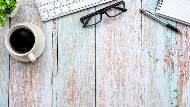 Widok z góry drewniany stół kubek kawy klawiatura okulary notebook miejsce kopia przestrzeń.