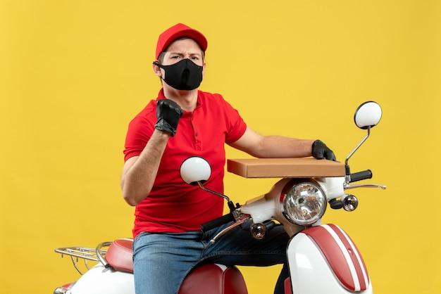 Widok z góry dumnego, ambitnego, emocjonalnego kuriera w czerwonej bluzce i rękawiczkach w masce medycznej siedzi na skuterze, pokazując porządek