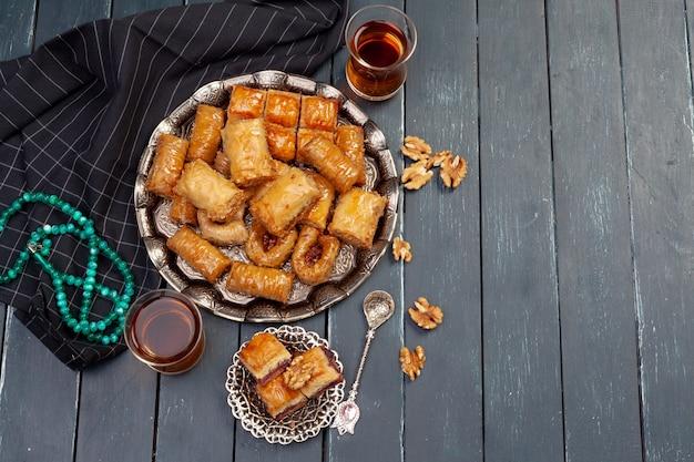 Widok z góry duża metalowa taca z turecką bakławą na deskowym drewnianym stole