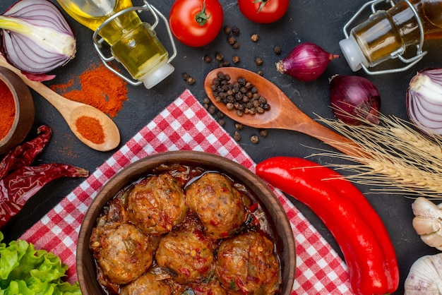 Widok z góry duża zupa z klopsików w misce czerwona papryka w proszku w małej misce sałata butelka cebula na stole