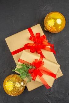 Widok z góry duże i małe prezenty świąteczne w brązowym papierze związane kulkami z czerwoną wstążką na ciemnej powierzchni