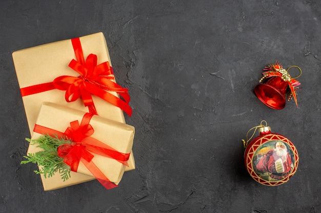 Widok z góry duże i małe rozmiary prezenty świąteczne w brązowym papierze związane z czerwoną wstążką zabawki choinkowe gałąź jodła na ciemnym tle