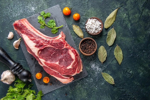 Widok z góry duży kawałek surowego mięsa z pieprzem i zieleniną na ciemnej powierzchni