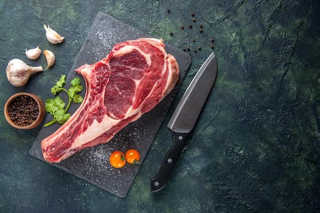 Widok z góry duży kawałek surowego mięsa z pieprzem na ciemnej powierzchni
