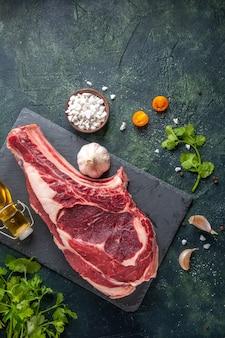 Widok z góry duży plaster mięsa surowego mięsa z zieleniną na ciemnej powierzchni