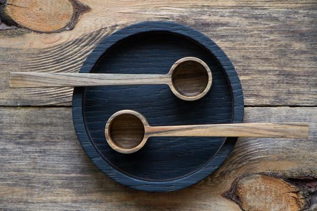Widok z góry dwie drewniane łyżki na czarnym talerzu na drewnianym stole