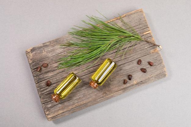 Widok z góry dwie małe szklane butelki olejku cedrowego na starej desce z gałązką cedrową i orzechami na szarym tle. koncepcja produktów iglastych spa aromaterapii i spa.