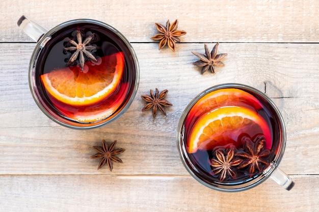 Widok z góry dwie szklanki grzanego wina z przyprawami i plasterkami pomarańczy na drewnianym stole, widok z góry