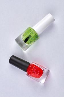 Widok z góry dwóch butelek do paznokci na białym tle. zielone i czerwone butelki z lakierem do paznokci.