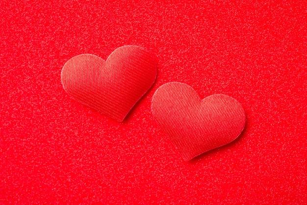 Widok z góry dwóch czerwonych ozdobnych serc na czerwonym tle